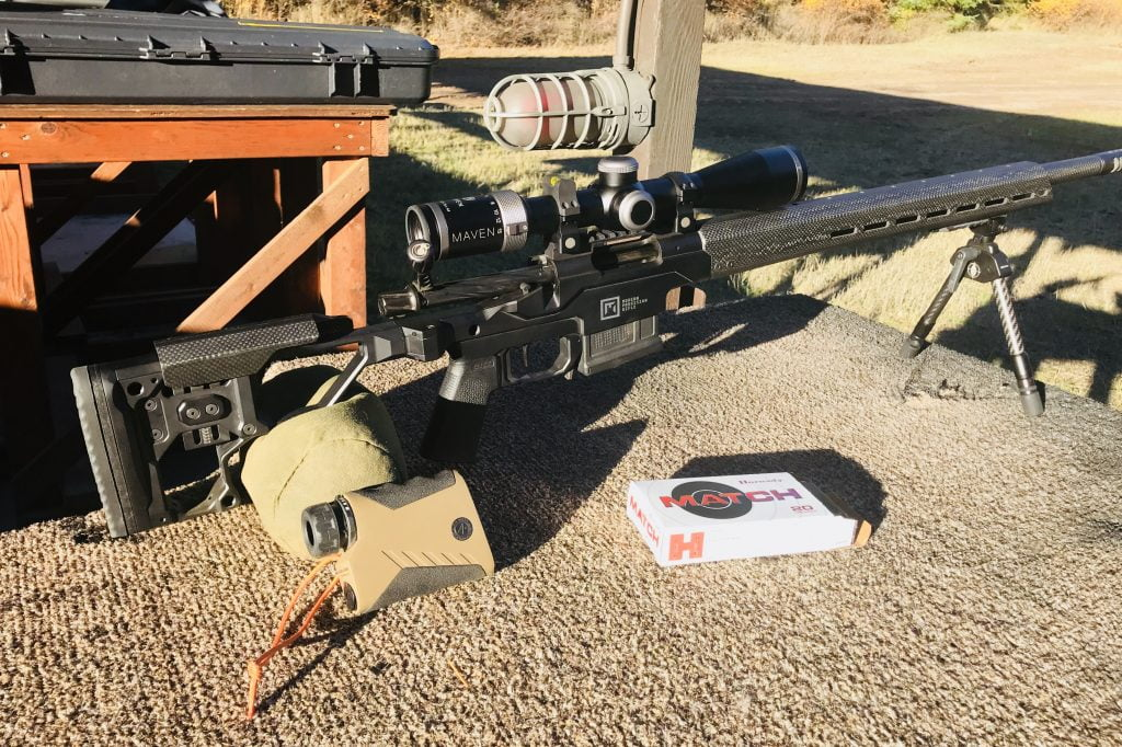 Picture of a scoped rifle sitting on a shooting bench with a rangefinder and box of bullets.